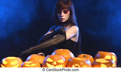 Woman Halloween pumpkins - Woman with Halloween makeup with...