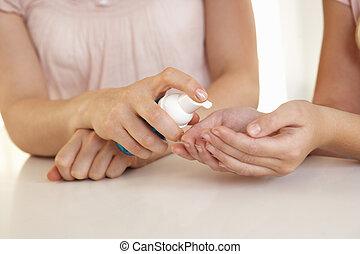 Woman hand applying hand sanitizer