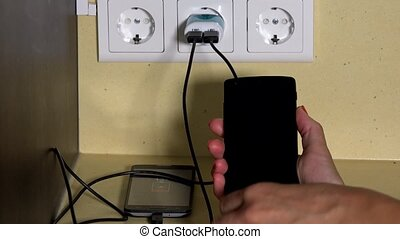 woman hand attach smart phone to wall charger and hold in hand. Battery charging status visible on screen. Closeup shot. 4K