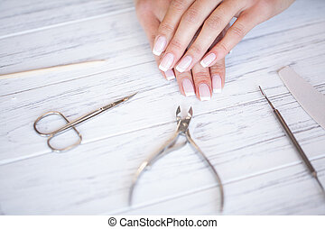 Woman Hand Care. Closeup Of Beautiful Female Hands Having Spa Manicure At Beauty Salon. Beautician Filing Clients Healthy Natural Nails With Nail File. Nail Treatment