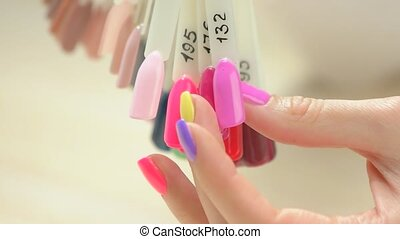 Woman hand choosing nail color. Slow motion female manicured...