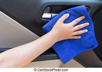 Woman hand cleaning interior car door panel with microfiber cloth