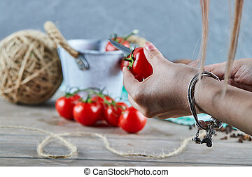Woman hand cutting red tomato into two pieces with knife