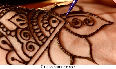 Woman hand decorated with henna tattoo, mehendi, on black, close up, cam moves top down
