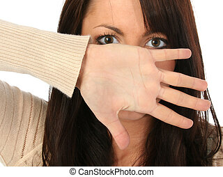 Beautiful young woman hiding behind hand. Open palm flat towards camera.