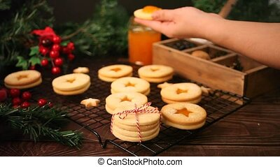 Woman hand filled with apricot jam a traditional Austrian Christmas cookies Linzer biscuits
