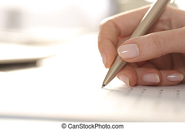 Woman hand filling out form with pen on a desk