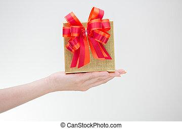 Woman hand hoding golden gift box