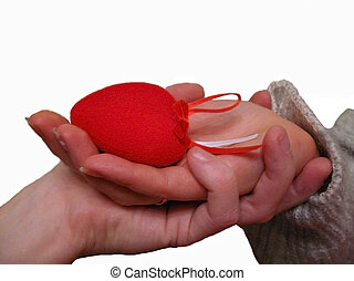 Woman hand hold a Valentine heart with a help of mans hand