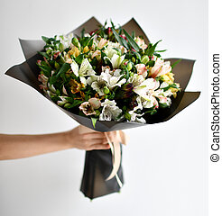 Woman hand hold bouquet of flowers white grey