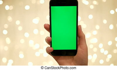 Woman hand hold smart phone on abstract blurred bokeh of light background background..Green screen Chroma Key. Close up. Tracking motion. Vertical