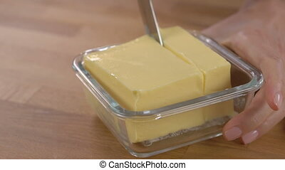 Woman hand hold the knife cutting the butter