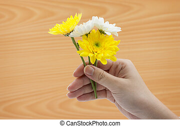 Woman hand holding a bunch of flowers On wooden background