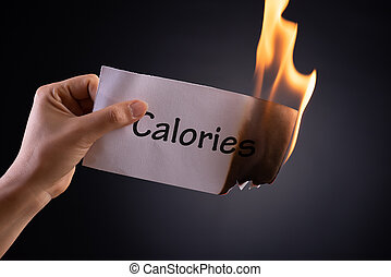 Woman hand holding a burning piece of paper with the word calories. Healthcare concept.