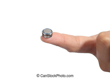 Woman hand holding a button battery with the forefinger...