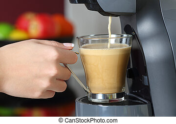 Woman hand holding a cup in a coffee maker