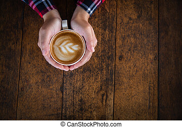 Woman hand holding a cup of coffee on an old wooden table, top view