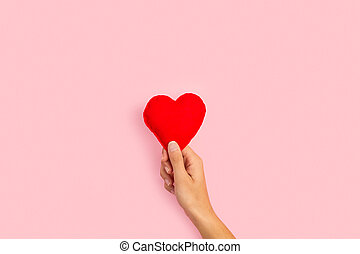 Woman hand holding a fabric red heart on a pink background