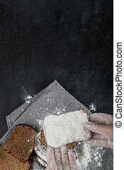 Woman hand holding a slice of bread with flour