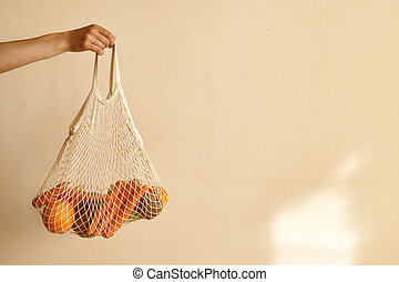 Woman hand holding a string shopping bag with vegetables, fruits in warm earthy tones, zero waste
