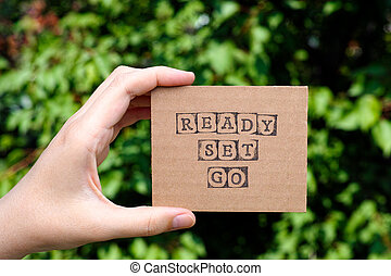 Woman hand holding cardboard card with words Ready Set Go