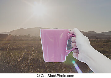 Woman hand holding coffee cup with sunrise