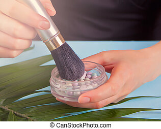 Woman hand holding makeup brush and ball pearl blush in a jar on the blue background