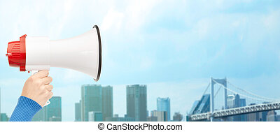 woman hand holding megaphone over city background