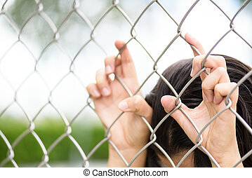 Woman hand holding on chain link fence for freedom, Human...