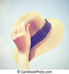 Woman hand holding panama hat with retro filter effect
