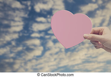 Woman hand holding pink heart