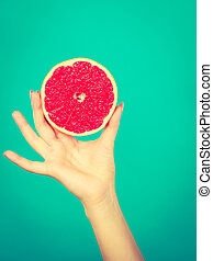 Woman hand holding red grapefruit