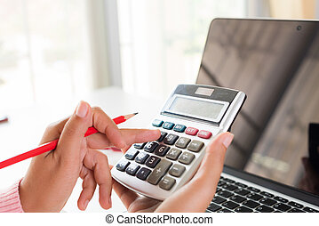 woman hand holding red pencil and working with calculator, business document and laptop computer notebook