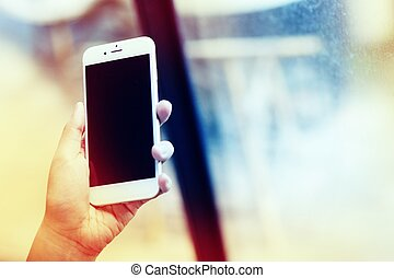 Woman hand holding smartphone against on smooth in coffee shop cafe background.