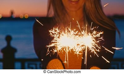 Woman hand holding sparkler outdoors in front of sunset sky...