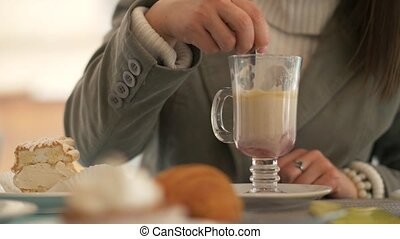Woman hand holding spoon and stirring coffee latte at table...