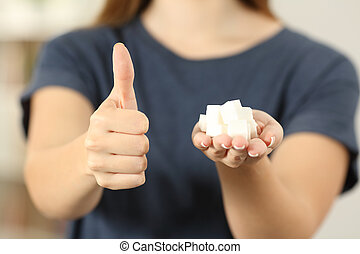 Woman hand holding sugar cubes with thumbs up