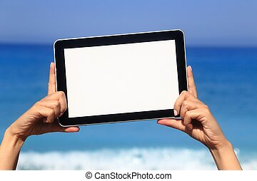 Woman hand holding tablet computer on the beach