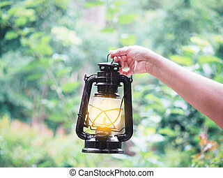 woman hand holding the old lamp in the forest.