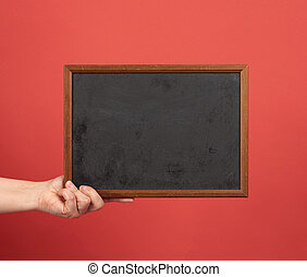 woman hand holds brown empty wooden frame on red background