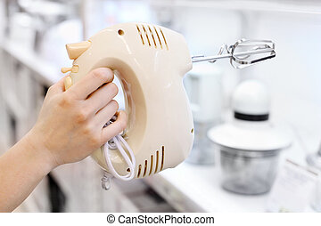 Woman hand holds mixer in supermarket; shallow depth of ...