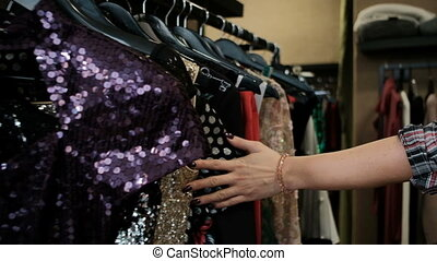 woman hand holds on clothes with bracelet, black manicure in...