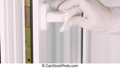 Woman hand in disposable glove closing a window