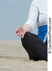 Woman hand in lotus yoga pose at the beach