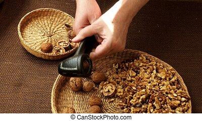 Woman hand is cracking a walnut with metal nutcracker