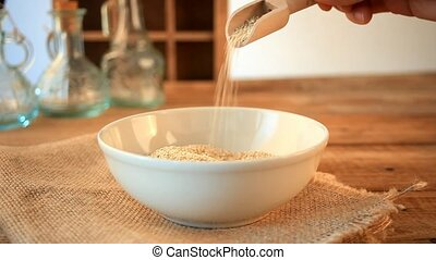 Woman hand is pouring quinoa grains with scoop on wooden...