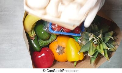 High angle view of woman hand laying fruits and vegetables out of cardboard bag. Healthy food home delivery concept