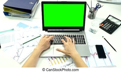 Woman hand on laptop keyboard with green screen monitor in the office