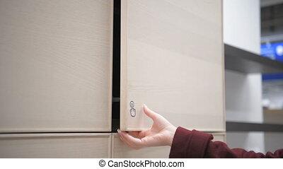 Woman hand opening kitchen cupboard door to check mechanism...