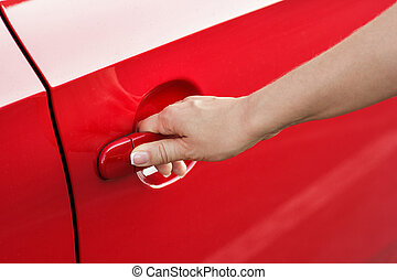 Woman hand opening red car door, close-up